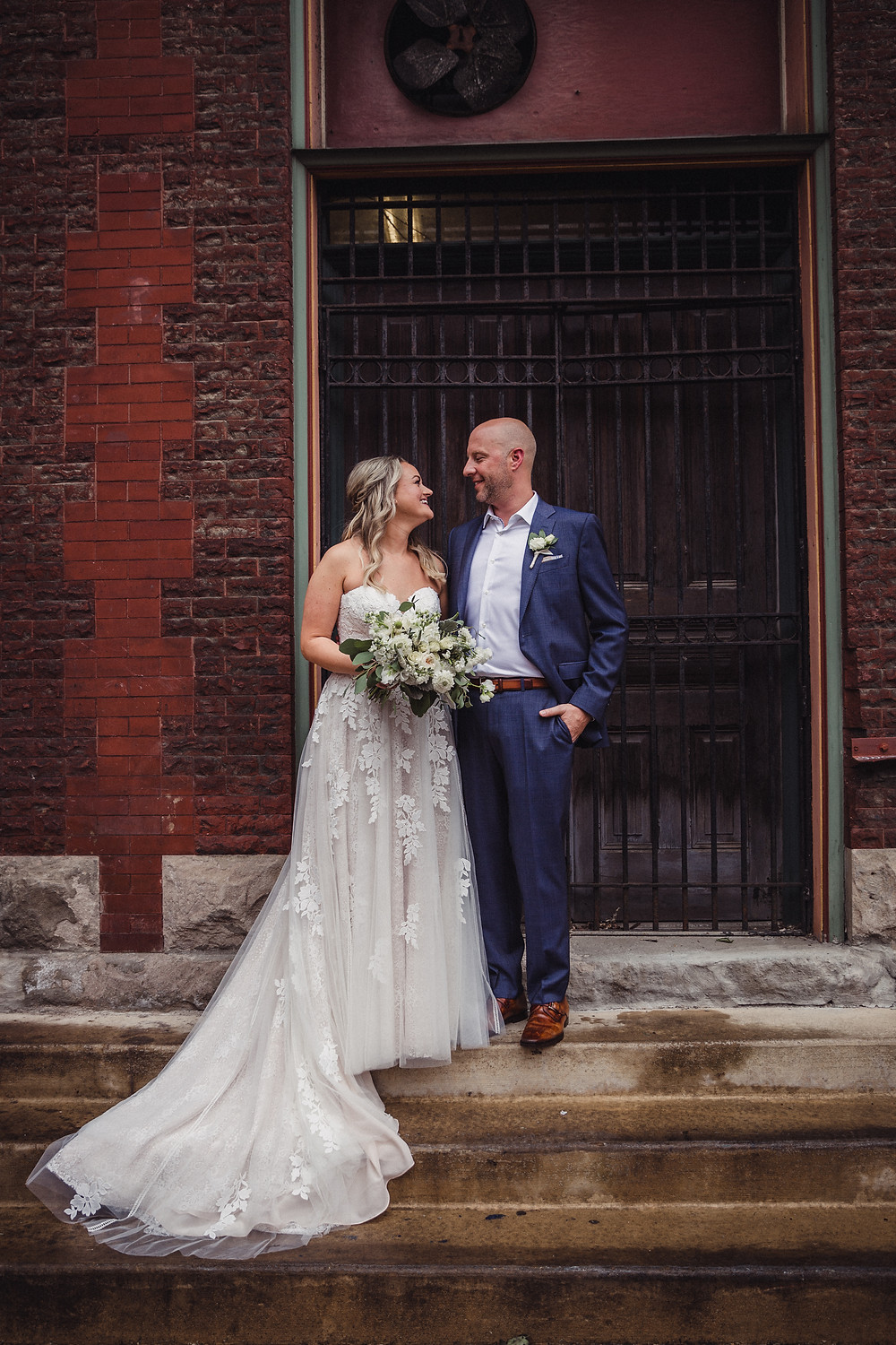 Bride and Groom on the steps of a nearby urban brick building