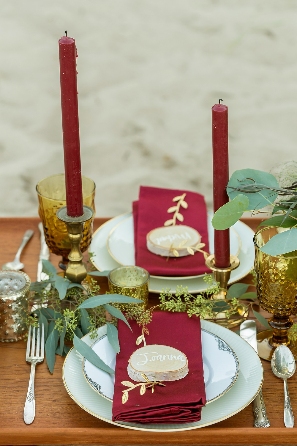Tablescape using vintage flatware, stemware, china, and burgundy candles for an upscale beach picnic