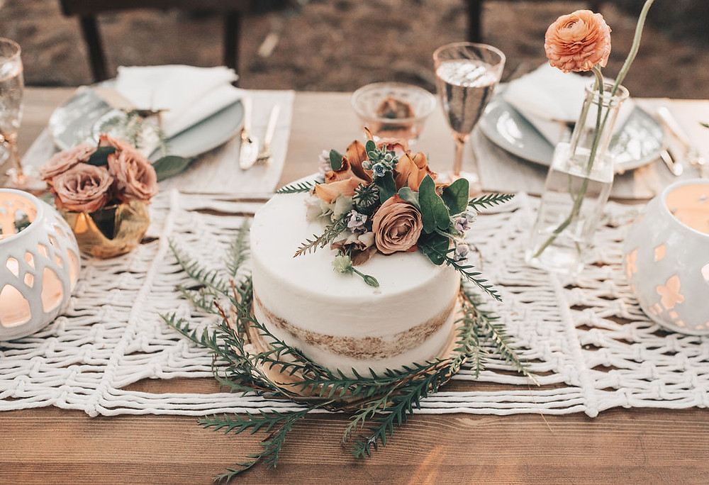 Naked cake displayed on macrame table runner for sweetheart table beauty