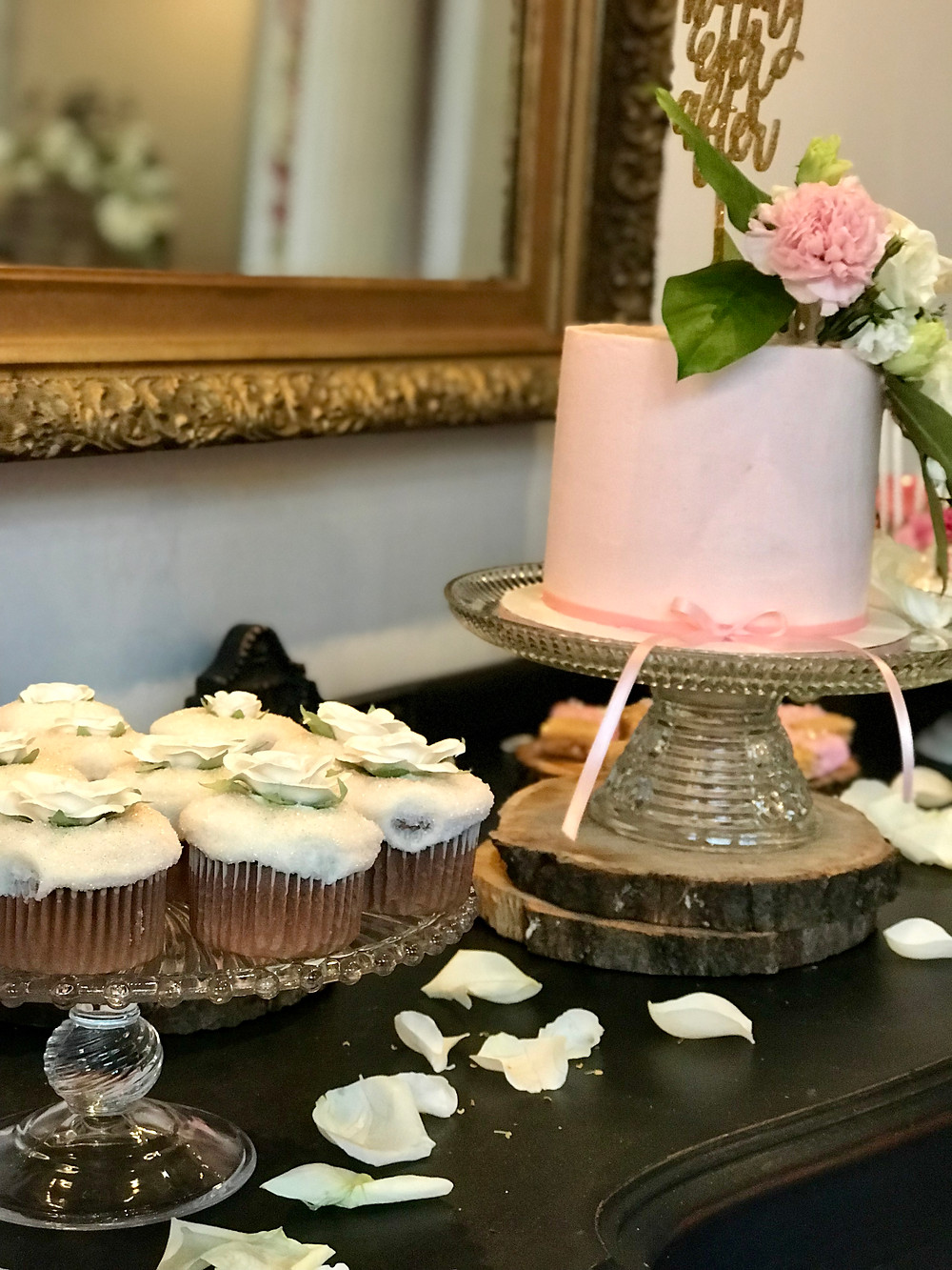 Scattered rose petals along with a display of cupcakes, cake pops and layered cake made the vintage buffet so elegant.