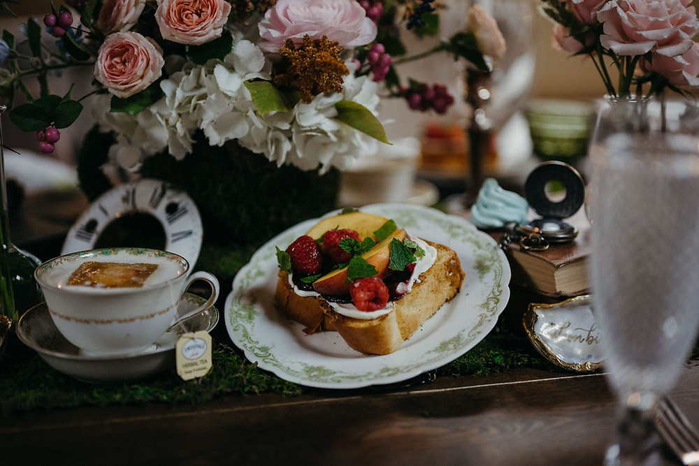 tablescape with teacups, vintage china, and moss covered teacup floral display