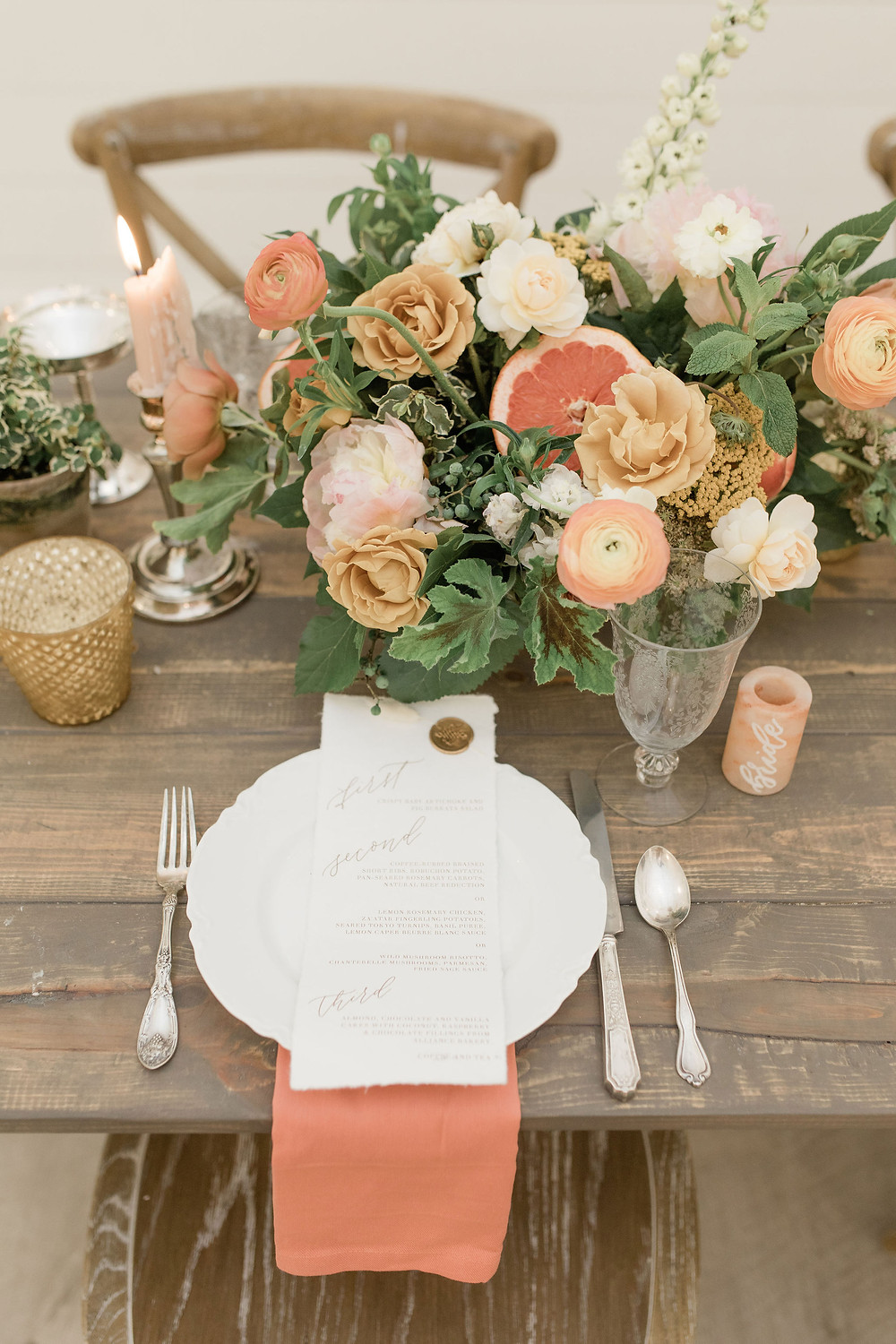 Farm table centerpiece showing details of fresh fruit among ranunculus, roses, and peonies, mint springs, and stock.