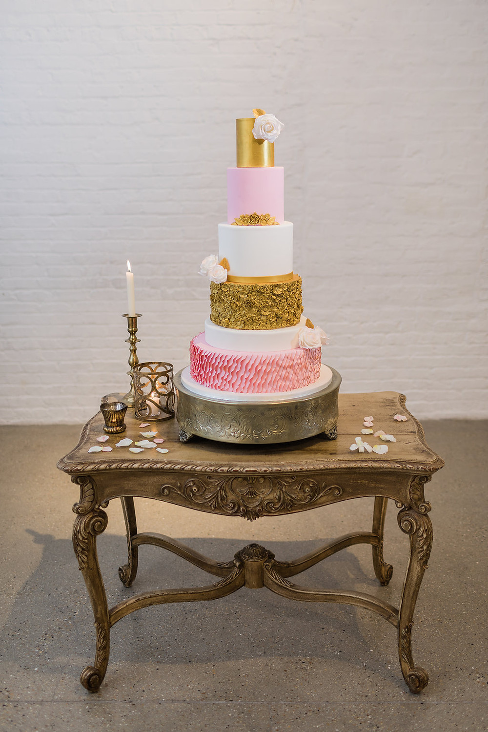 The French table serves as the cake table for this delicate 5 tiered wedding cake, accented with brass candleholders.