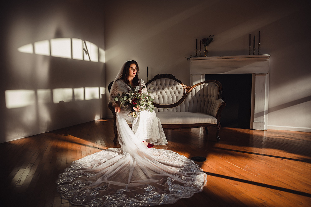 Bride in the shadows, while posing on our white vintage settee