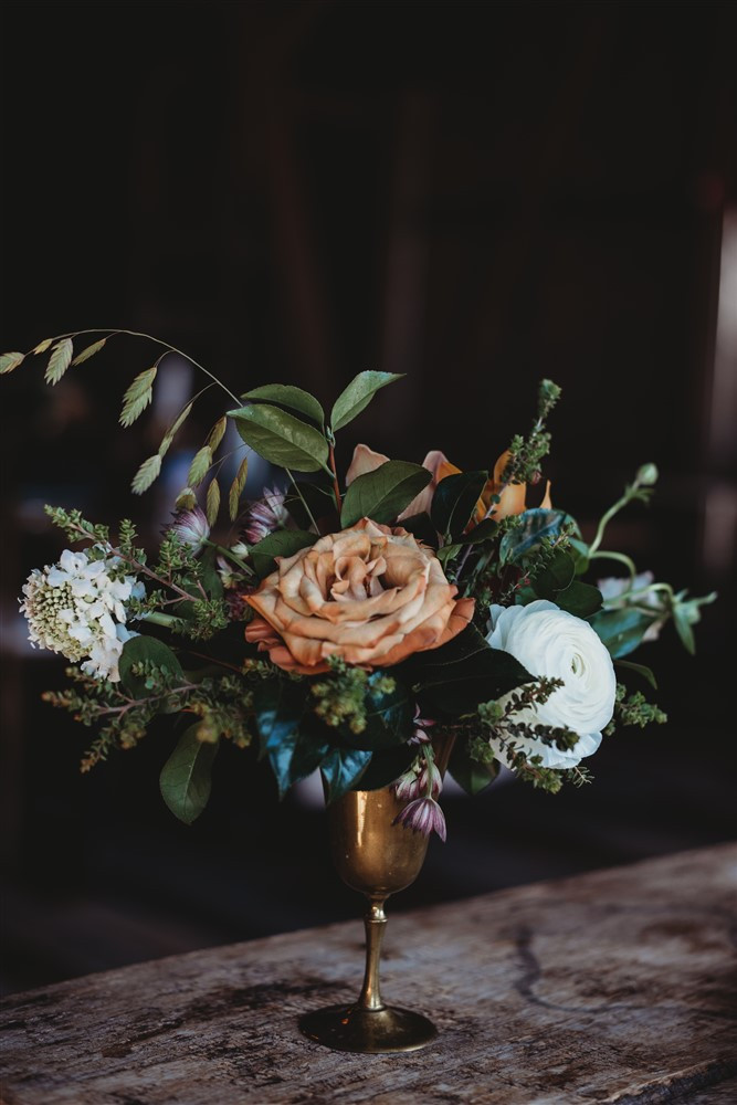 floral display in brass compote containing fall colors