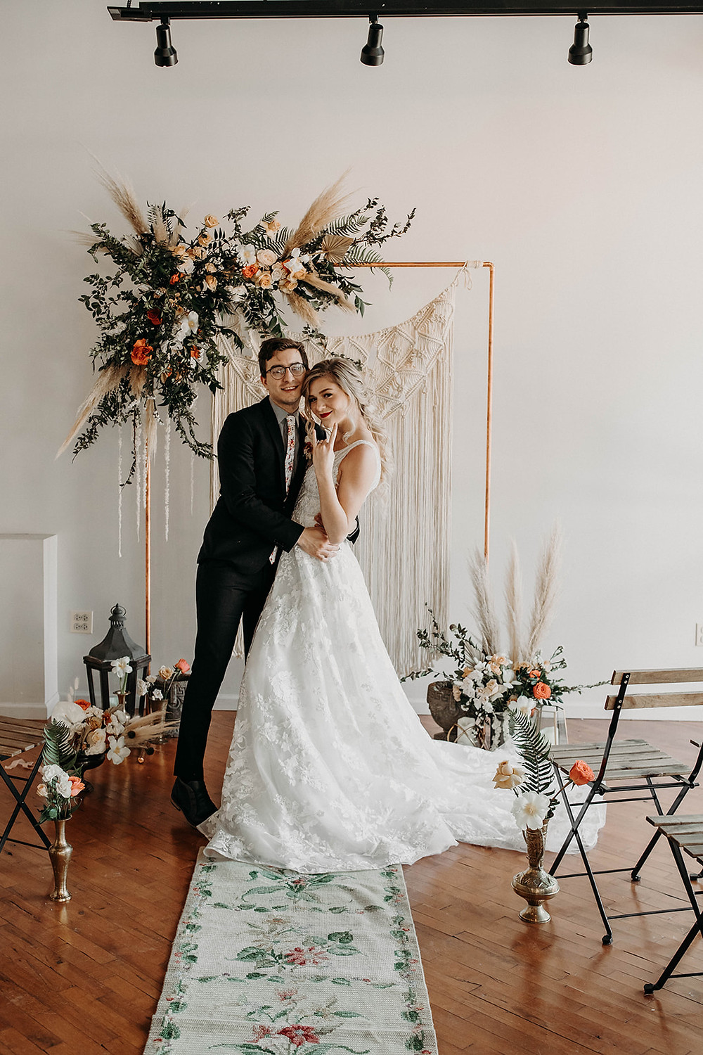 Bride and Groom pose at ceremony aisle with copper backdrop floral display behind them.