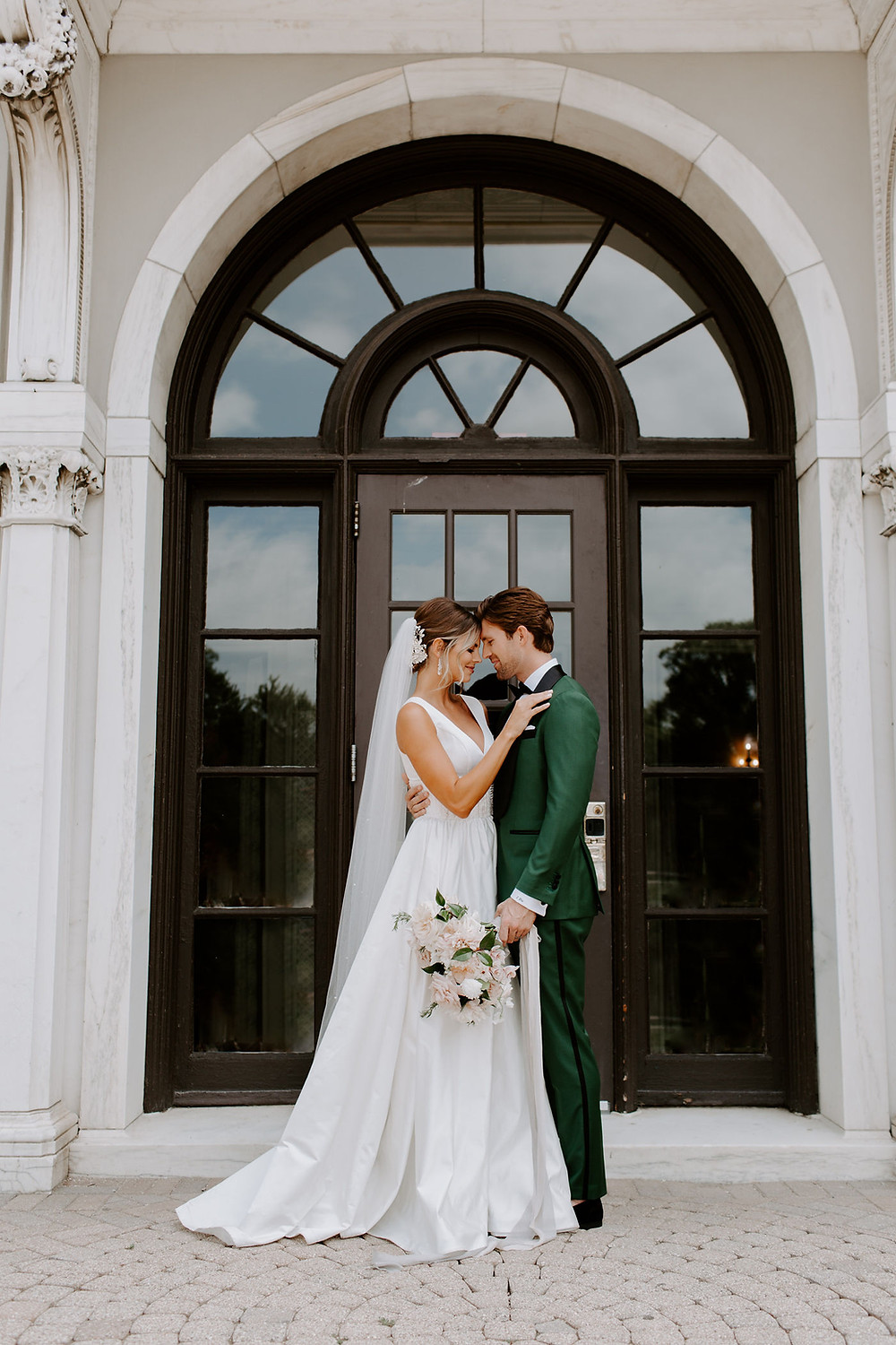 Bride and groom stand under arched doorway at Armour House
