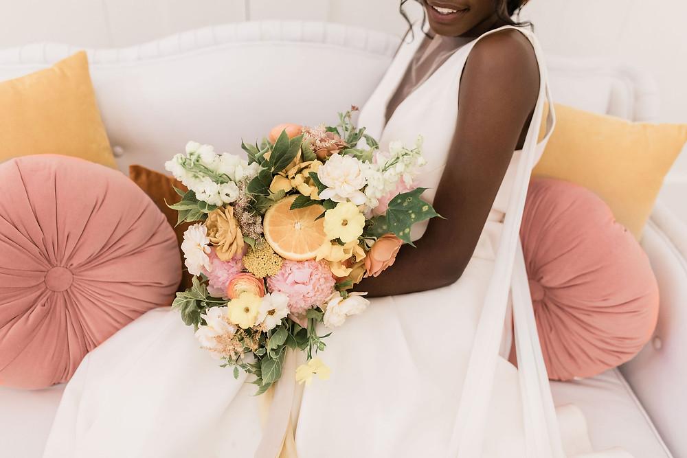 Tangerine, saffron, butterscotch pillows all accentuate the colors of the brides bouquet.