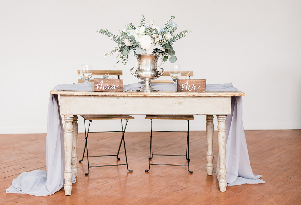 Wooden farm-style sweetheart table with modern bistro chairs
