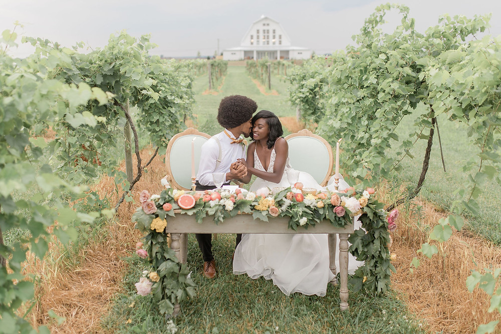 Sweetheart table with pistachio green chairs set in the vineyard for the reception