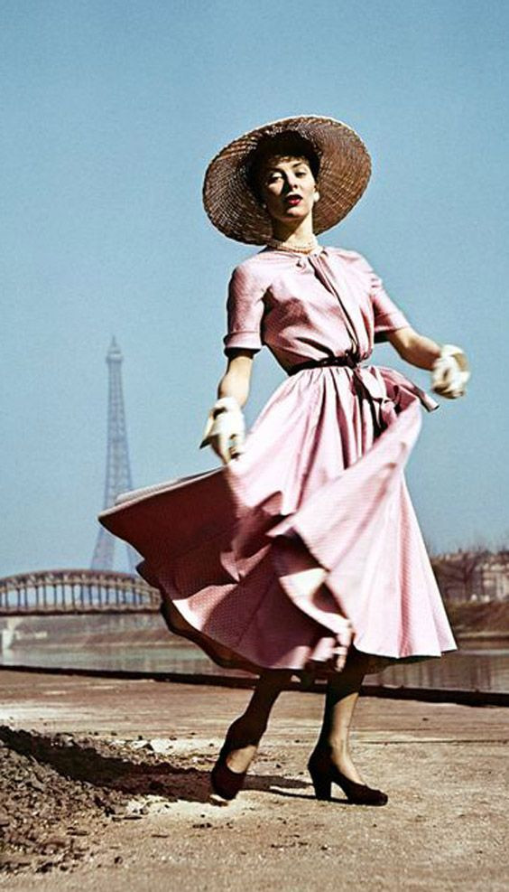 A stunning fashion photograph of a Christian Dior model wearing a pink swing dress and hat with the Eiffel Toer in the background