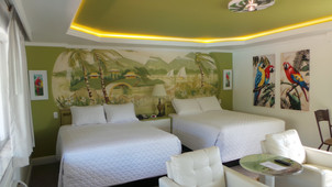 view of room with parrot pictures, preserved mural, 2 queen beds, night stand, TV chairs and table
