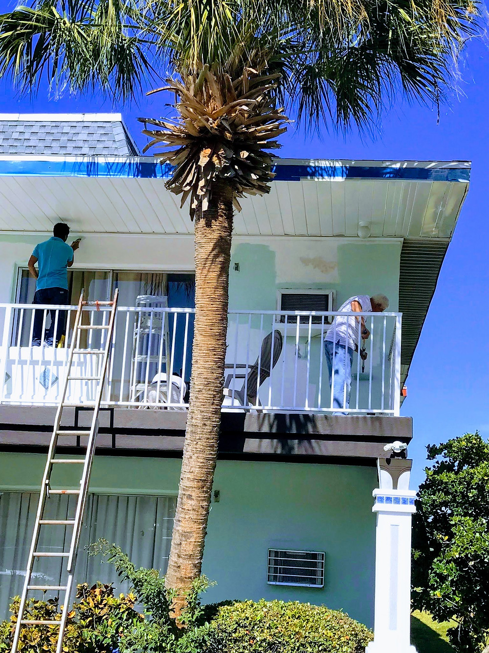 Photo of men painting on balcony