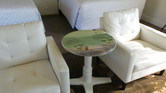 photo showcasing handpainted accent table between two comfortable chairs