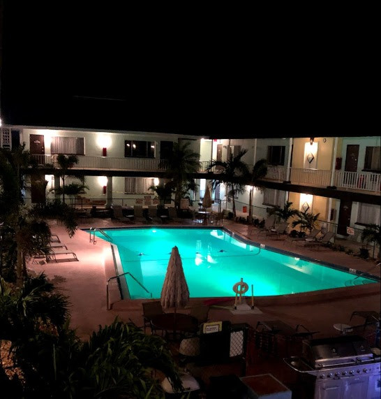Evening photo of pool, pool deck and courtyard with lights