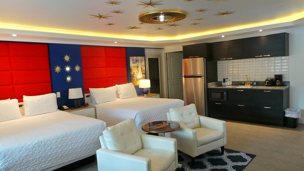 Studio room red, white and blue accented with stars on wall and ceiling. 2 Queen beds, TV chairs and table, Kitchenette with full refrigerator, cooktop, microwave, sink, coffee maker and cabinetry.