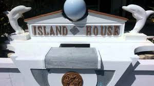 Island House sign surrounded by statues of dolphins