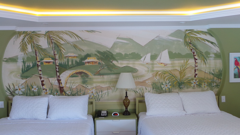 phto showcasing preserved tropical mural behind 2 queen beds with overhead lights and nightstand