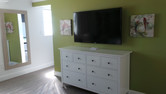 """photo showing dresser, 55"""" TV on wall and full length mirror"""