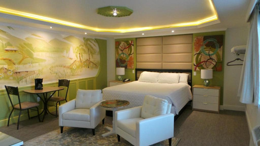 Photo of King room showing dining table chairs, TV chairs, table, bed, mural and overhead lighting