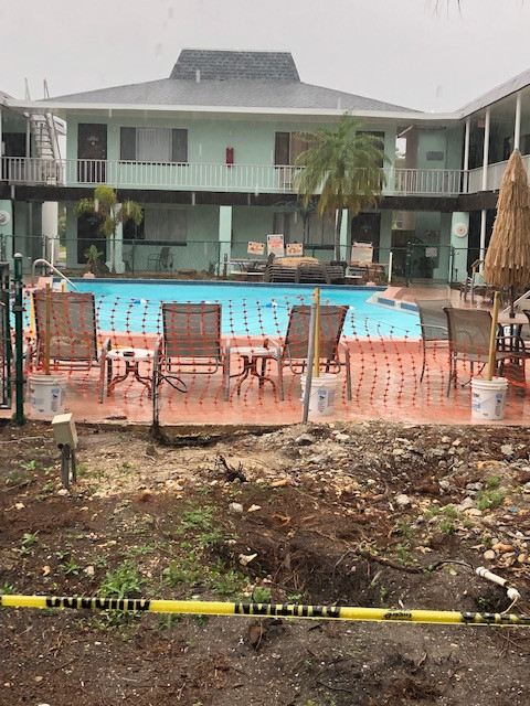 Construction photo showing dirt where deck was and orange fence surrounding the pool