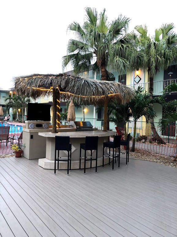 photo of new composite decking with Tiki Hut bar/grill area. Grill, 5 chairs, TV, radio and thatched roof