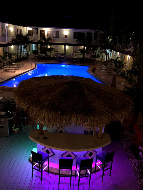 Photo looking down on Tiki Hut across the pool, surrounded by lounge chairs, at night