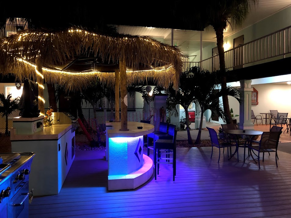 Photo of Tiki Hut with lights showing seating on deck, partial views of 2 of 3 available grills