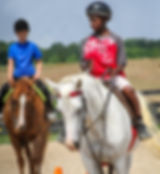 Campers learning to guide their horses through cones