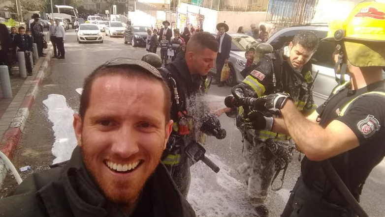 Sam McCartney with a group of firefighters dousing themselves with water