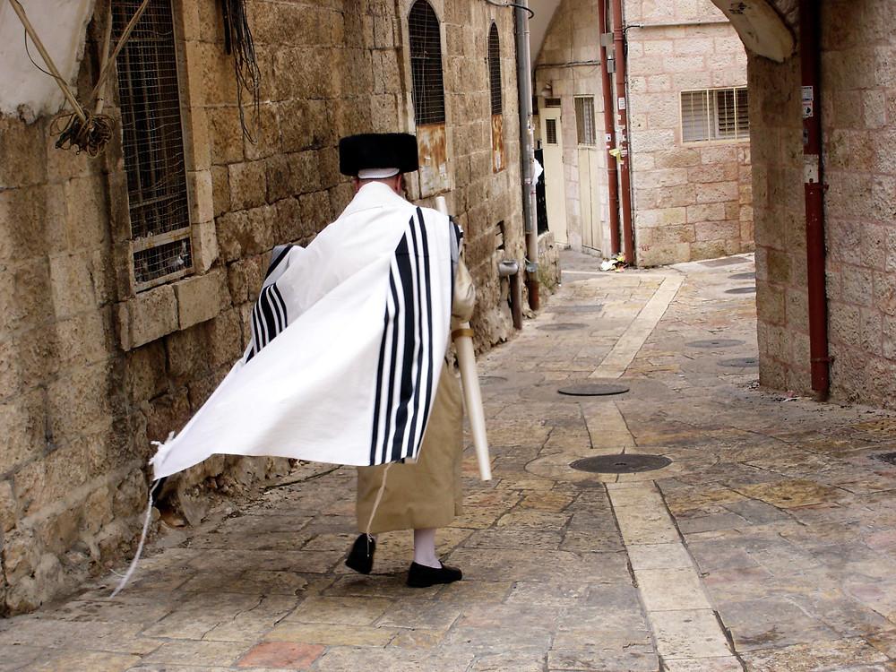 A Jewish man wearing a streimel and tallit walking through the Old City in Jerusalem