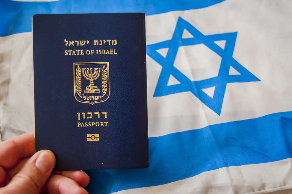 An Israeli passport in front of an Israeli flag