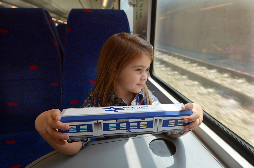 A young girl holding a model of an Israeli Railway Train