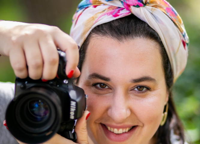 Lisa Rich of Lisa Rich Photography holding up a camera