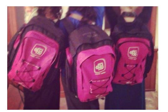 Three girls wearing large pink Sheirut Leumi backpacks