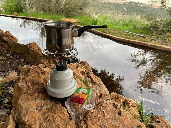 Making hot coffee with a pakal kafe kit at the banks of Ein Shir