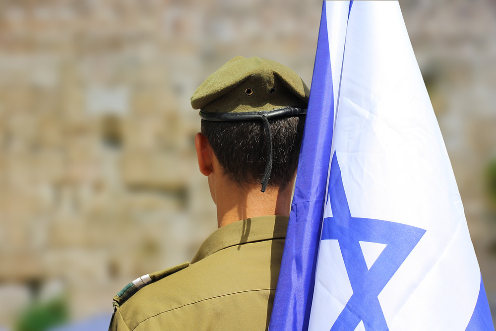 The back of an IDF soldier wearing a green uniform and beret while holding an Israeli flag over his right shoulder.