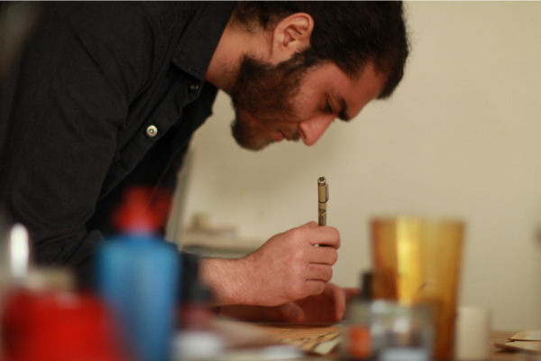 Peter Shamah holding a pen and studying his artwork