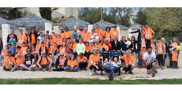 Large group of Team Shira members wearing orange shirts at the Jerusalem Marathon