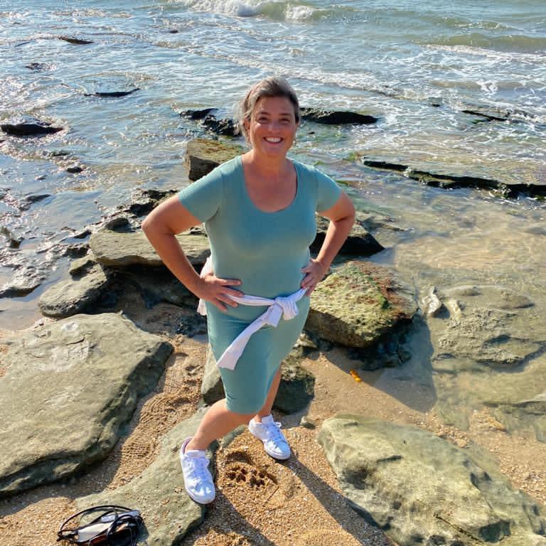 Deborah Michael standing on rocks at the seashore