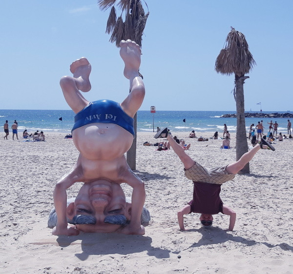 A young man performing a headstand on the sand next to a sculpture of Ben Gurion on his head