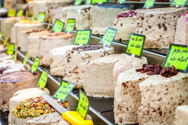 Rows of Israeli halva cakes lined up with small signs on each dessert