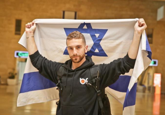 Oleh Simcha Brodsky in Ben Gurion Airport holding up an Israeli flag