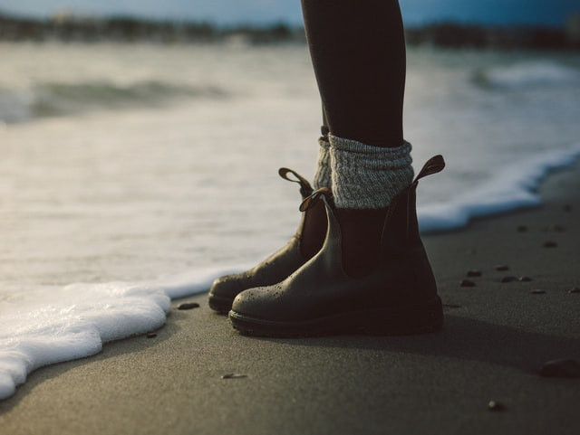 A woman wearing blundstone shoes with thick socks at the edge of the sea