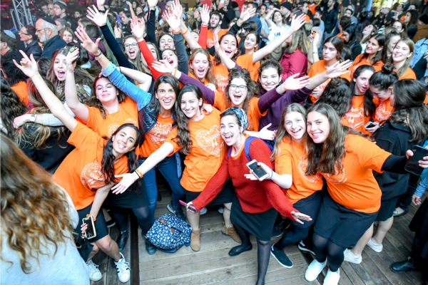 Orly Wahba posing with a crowd of smiling young women with raised arms
