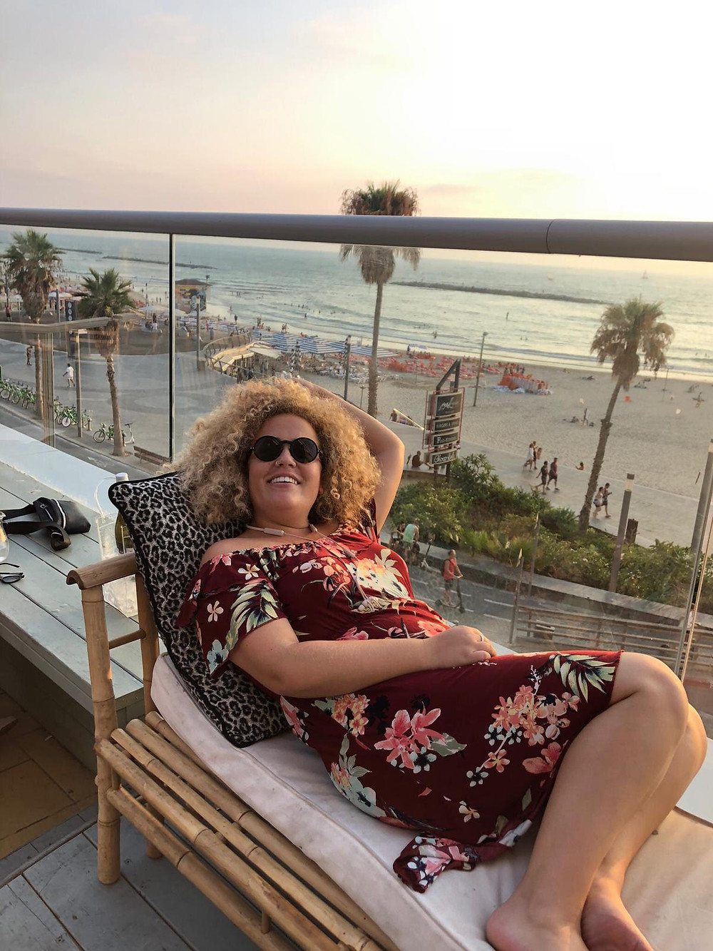Oleh Breanna Stein laying on a cushioned bench overlooking the sea