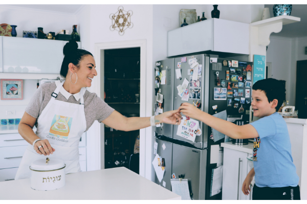 Elyse Shahar, owner of the Cookie Goodness, handing her son a cookie to taste in her kitchen