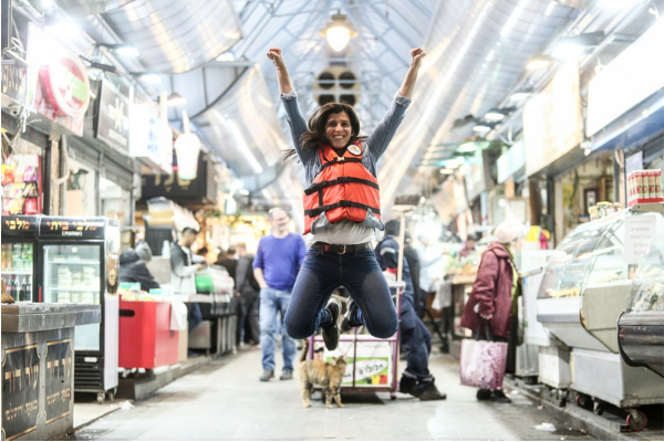 Orly Wahba wearing an orange life vest jumping with her arms raised inside the Mahane Yehuda Shuk