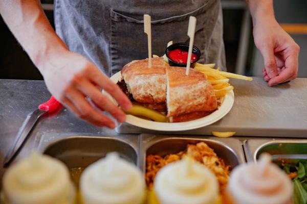A Hatch Brewery worker arranging a sandwich on a plate
