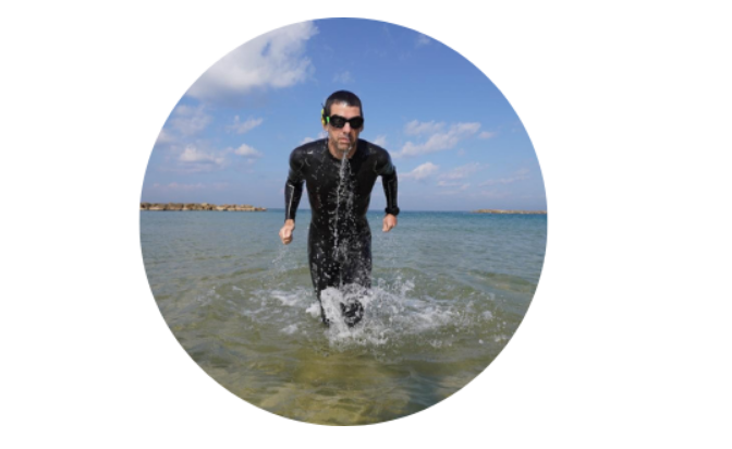 Oleh Frederic Simon coming out of the sea in a black wetsuit and goggles